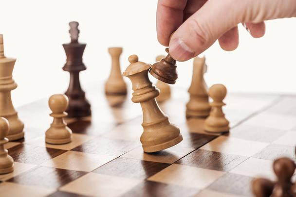 partial view of man doing move with brown pawn on wooden chessboard isolated on white - Photo, Image
