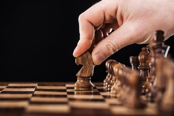 cropped view of man doing move with knight on wooden chessboard isolated on black - Photo, Image