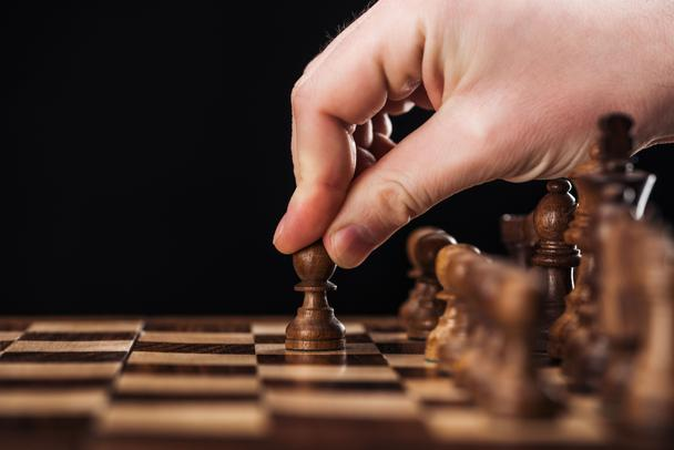 cropped view of man doing move with pawn on wooden chessboard isolated on black - Photo, Image