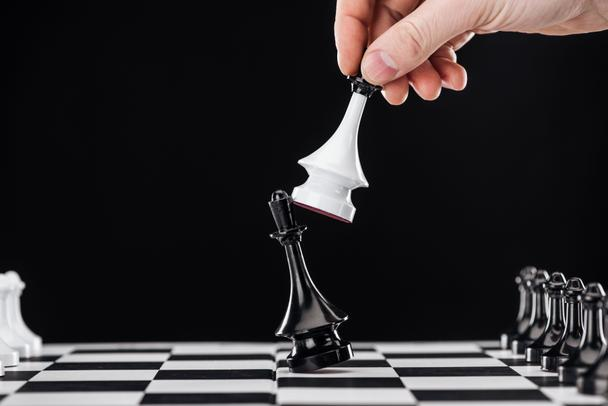 cropped view of man doing move with queen on chessboard isolated on black - Photo, Image