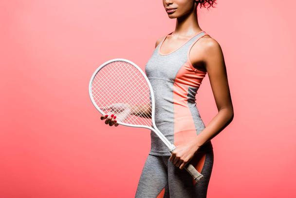 cropped view of african american sportswoman holding tennis racket isolated on coral with copy space - Photo, Image