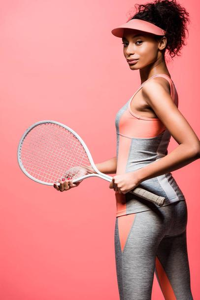 beautiful african american sportswoman in sun visor holding tennis racket and looking at camera isolated on coral - Photo, Image