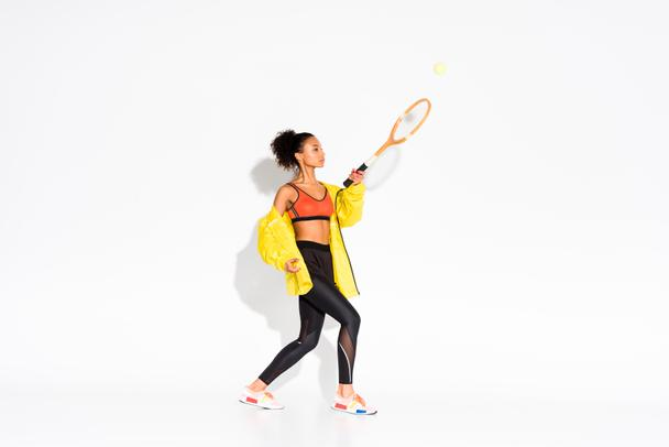 athletic african american sportswoman exercising with tennis racket and ball on white  - Photo, Image