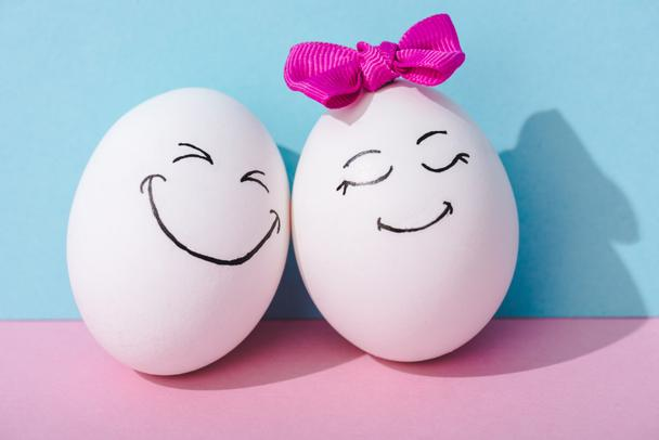 egg with bow and egg with happy face expression on blue and pink - Photo, Image
