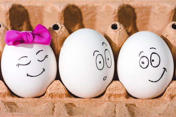 close up of eggs with smiling and shocked face expressions in egg carton  - Photo, Image