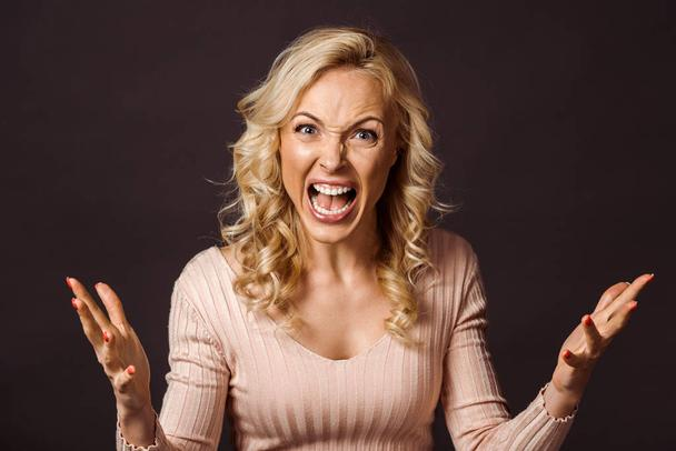 emotional blonde woman gesturing and screaming isolated on black  - Photo, Image