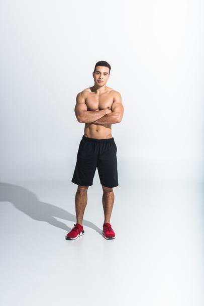 handsome sportive mixed race man in black shorts and red sneakers looking at camera on white - Photo, Image