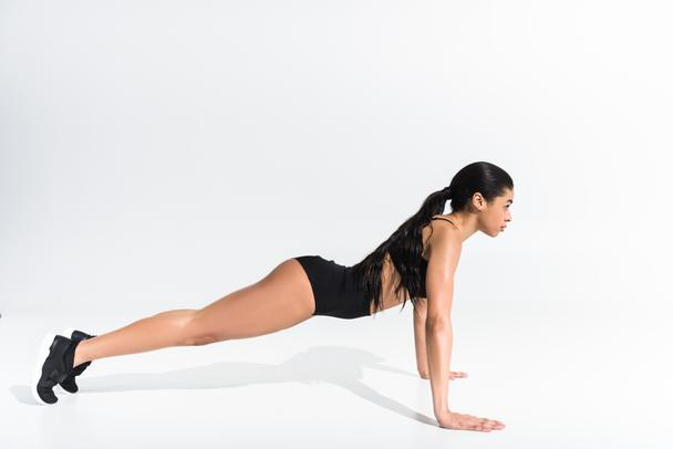 side view of sportive african american girl doing push ups on white background - Photo, Image