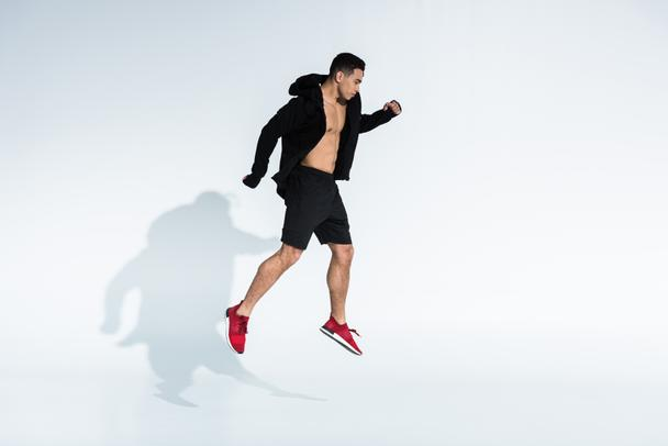handsome mixed race man in black sports jacket, shorts and red sneakers jumping on white - Photo, Image