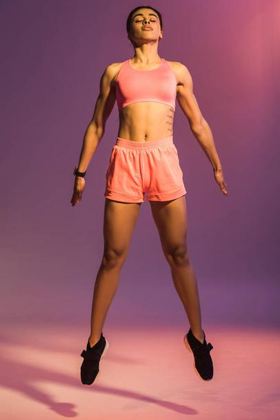 attractive african american girl in pink sports bra and black sneakers jumping with closed eyes on purple background - Photo, Image