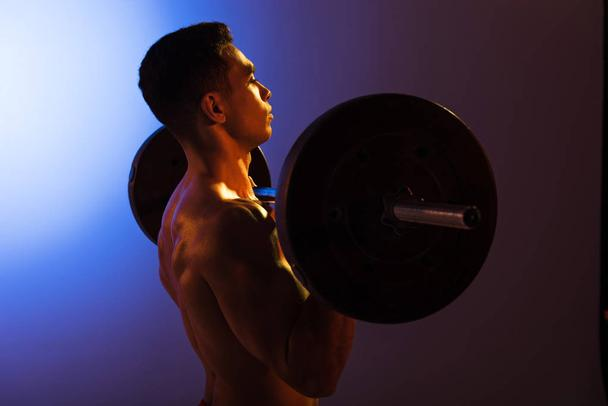 handsome athletic man lifting barbell on blue and dark purple gradient background - Photo, Image