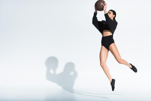 sportive african american girl in black sportswear and sneakers jumping with ball on white background - Photo, Image
