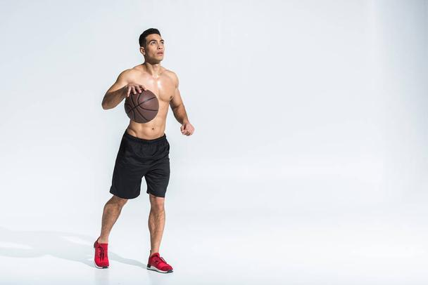 handsome athletic mixed race man in black shorts and red sneakers playing ball on white - Photo, Image