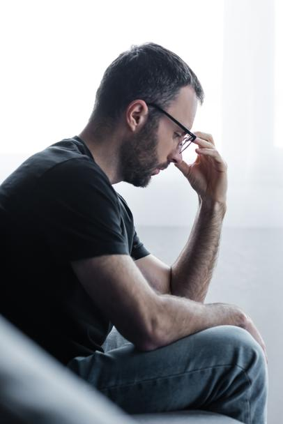 selective focus of sad bearded man in glasses holding hand near face - Photo, Image