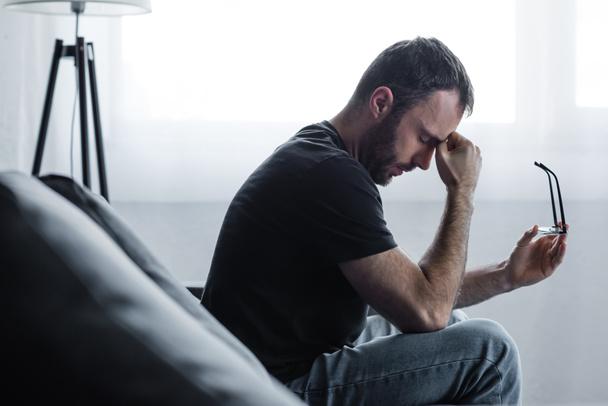 upset man sitting on sofa with closed eyes and holding glasses - Photo, Image