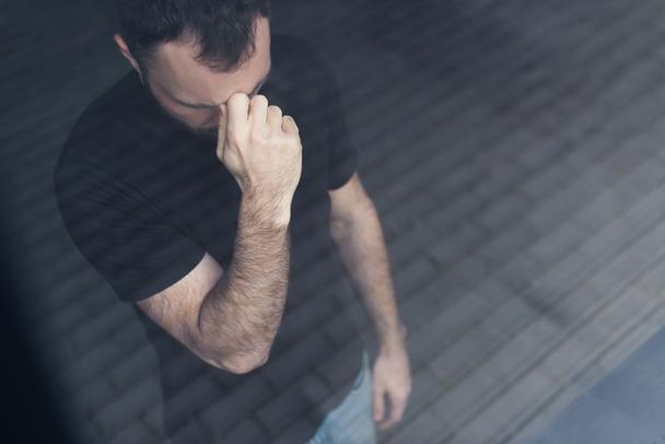 high angle view of depressed man in black t-shirt standing by window and holding hand near face - Photo, Image