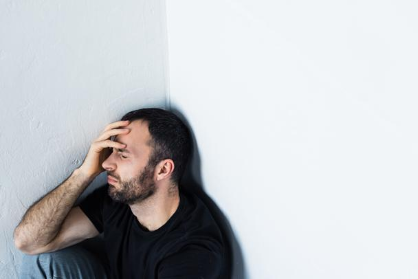 depressed man sitting in corner with closed eyes and holding hand on forehead - Photo, Image