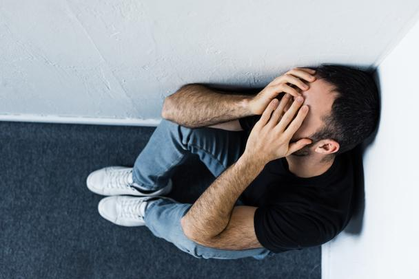 top view of upset man sitting on floor and corner and covering face with hands - Photo, Image