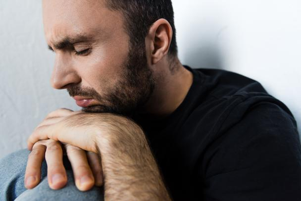 adult depressed man suffering while sitting by white wall with closed eyes - Photo, Image