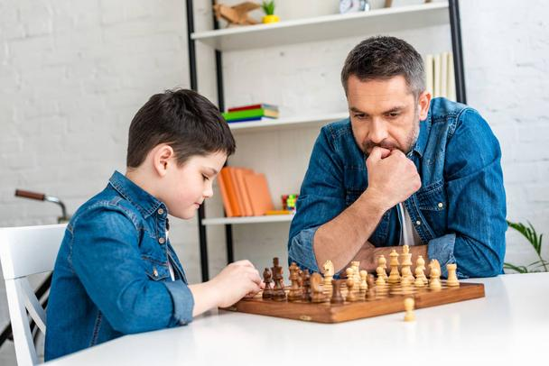 pensive father and son in denim playing chess while sitting at table at home - Photo, Image