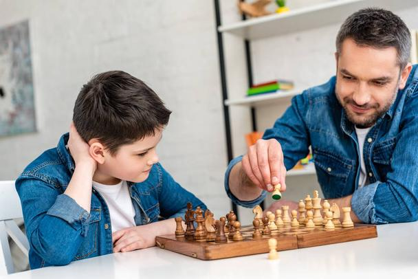father and son in denim sitting at table and playing chess at home - Photo, Image