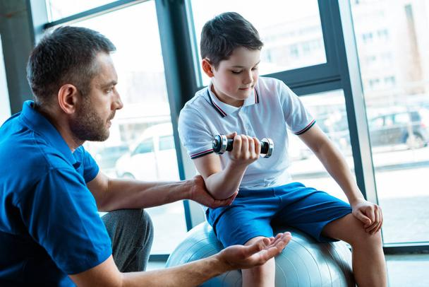 handsome father helping son exercising with dumbbell at gym - Photo, Image