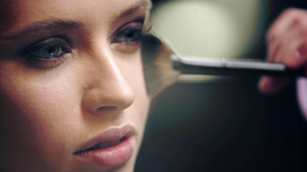 close up of makeup artist powdering model face with cosmetic brush - Footage, Video