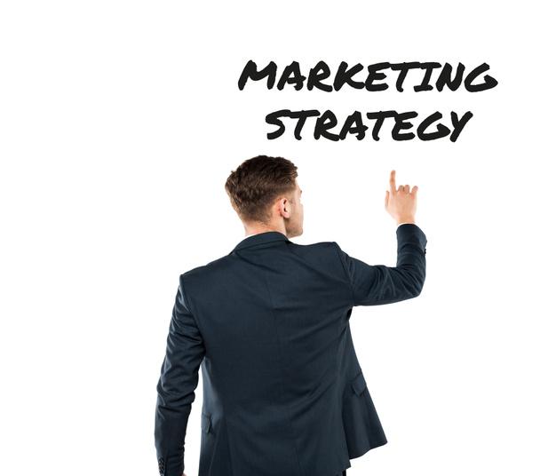 Achteraanzicht van de mens wijzend met de vinger op marketing strategie belettering op wit  - Foto, afbeelding