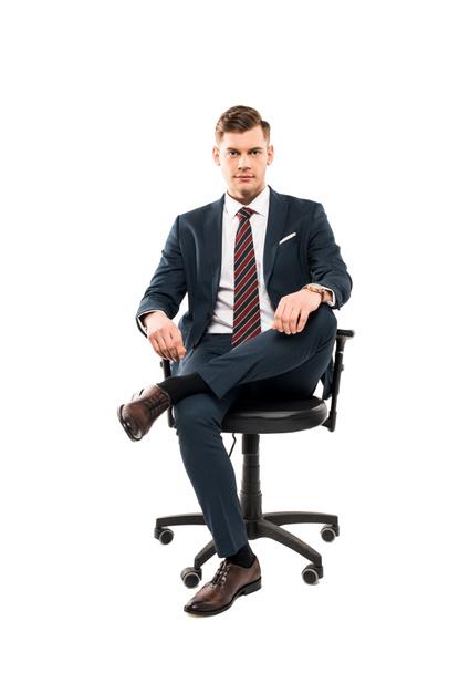 впевнений бізнесмен сидить на кріслі і дивиться на камеру ізольованою на білому  - Фото, зображення