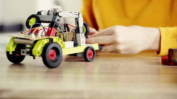 cropped view of child playing with electric car made of building blocks on table near books - Footage, Video