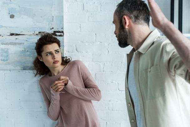 selective focus of scared woman looking at aggressive husband gesturing at home  - Photo, Image