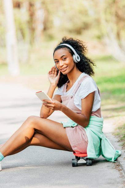 smiling african american girl listening music in headphones and using smartphone while sitting on penny board - Photo, Image