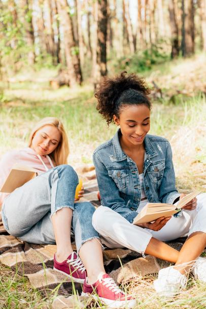 two multiethnic friends sitting on plaid blanket and reading books - Photo, Image