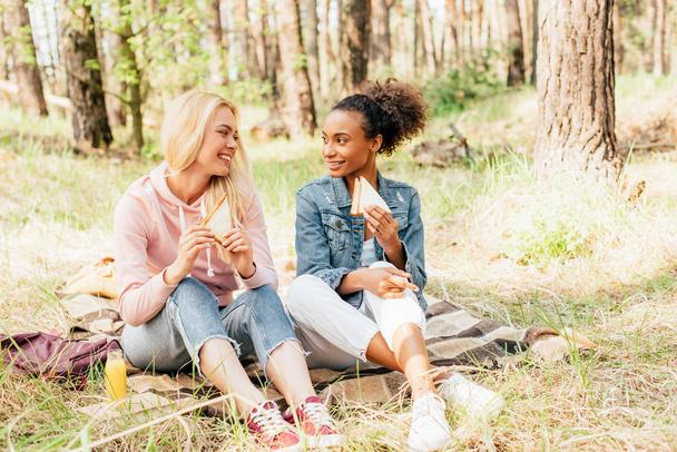 two smiling multiethnic friends sitting on plaid blanket with sandwiches and looking at each other - Photo, Image