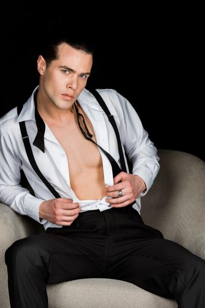 confident muscular man in white shirt and suspenders sitting in armchair isolated on black   - Photo, Image