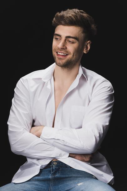 cheerful handsome man in white shirt smiling and looking away isolated on black - Photo, Image