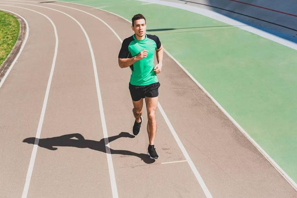full length view of mixed race sportsman running at stadium - Photo, Image