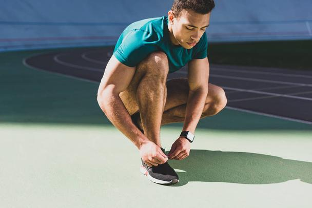 mixed race sportsman lacing up sneakers at stadium in sunny weather - Photo, Image