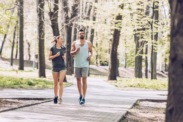 handsome man and pretty woman smiling while running in green sunny park  - Photo, Image