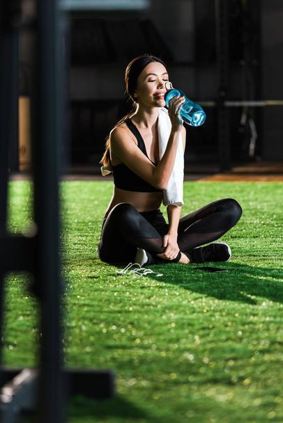 selective focus of cheerful woman sitting on grass and drinking water  - Photo, Image