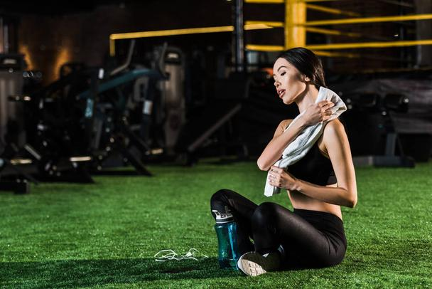 athletic woman holding towel while sitting with crossed legs on grass  - Photo, Image