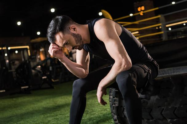 handsome and tired athletic man sitting on car tire in gym  - Photo, Image