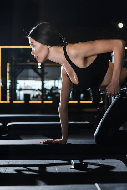 pretty and athletic woman working out with dumbbell in gym  - Photo, Image