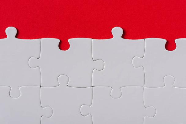 top view of matched white jigsaw puzzle pieces isolated on red  - Photo, Image