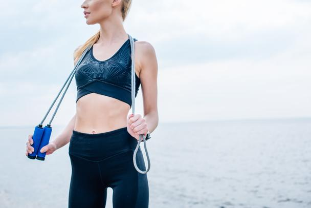 cropped view of girl in sportswear holding skipping rope near sea  - Photo, Image
