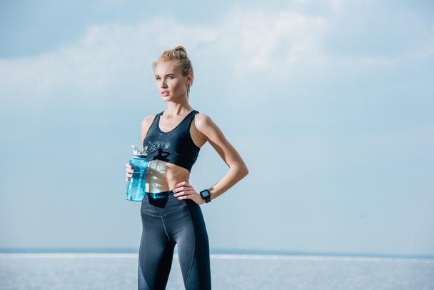 attractive and athletic girl holding sport bottle while standing with hand on hip near sea  - Photo, Image