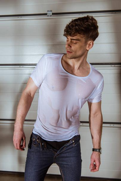 handsome man in jeans and wet white t-shirt - Photo, Image