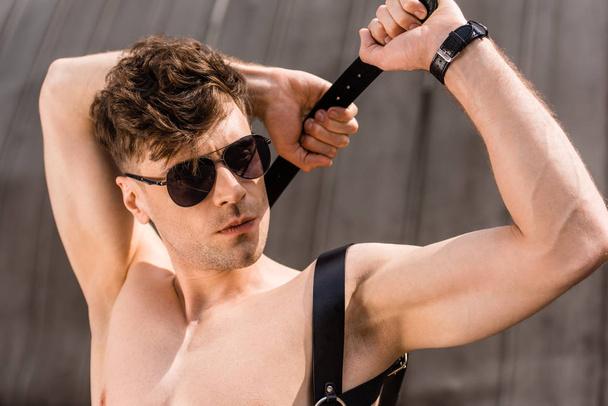 stylish sexy man in black sunglasses and sword belt - Photo, Image