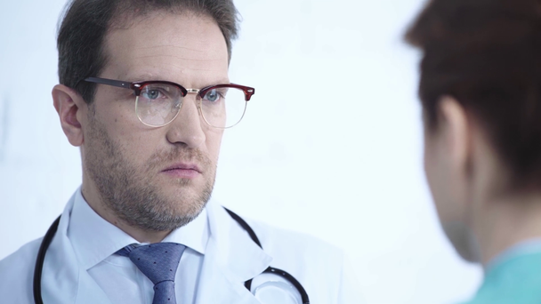selective focus of handsome doctor in glasses talking to nurse in hospital - Footage, Video