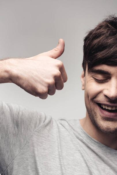 cheerful man showing thumb up isolated on grey, human emotion and expression concept - Photo, Image